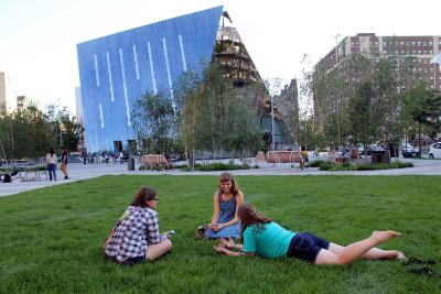 Three Case Western Reserve University students laying on the grassy area in Toby's Plaza in Uptown Cleveland with MOCA Cleveland in the background