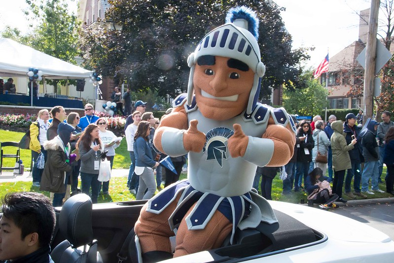 Spartan mascot giving the thumbs up while sitting on a car in a parade