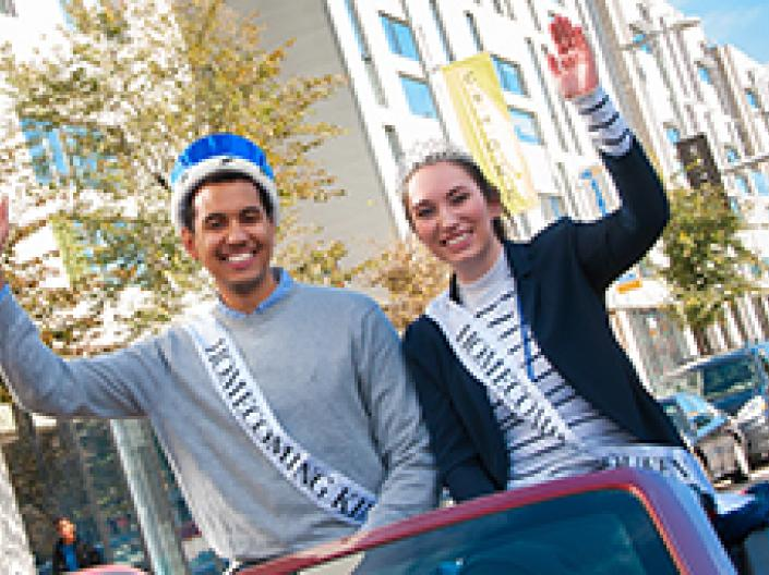 Case Western Reserve University homecoming king and queen riding in a car in the parade