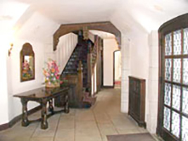 Interior of CWRU Manor House, with white walls and dark wood staircase