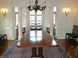 Interior of CWRU Manor House, with white walls and dark wood floor and table, with candelabra and rug
