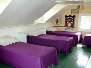 View of CWRU Pink Pig cottag bedroom, with three beds and wooden floor
