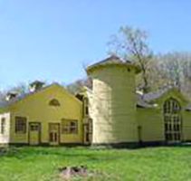 Outside view of Dairy Barn (Silo Theater) at CWRU Farm, in yellow with bare trees in the background