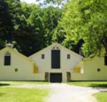 Outside view of Horse Barn at CWRU Farm, with tall green trees in background