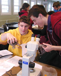 Two students working with papers and a microscope