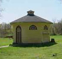 Outside view of Dovecote at CWRU Farm, a small circular structure in yellow with grey roof