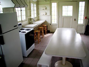 View of CWRU Pink Pig cottage kitchen, with white walls, tables and appliances