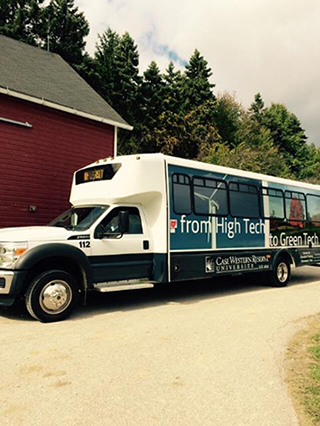 Shuttle Bus for Case Western Reserve University with text from High Tech to Green Tech written on side, parked in front of red barn with tall trees in background