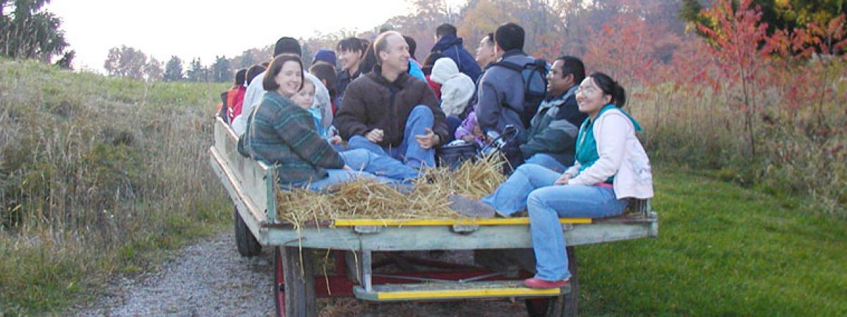People of all ages on a hayride through the countryside