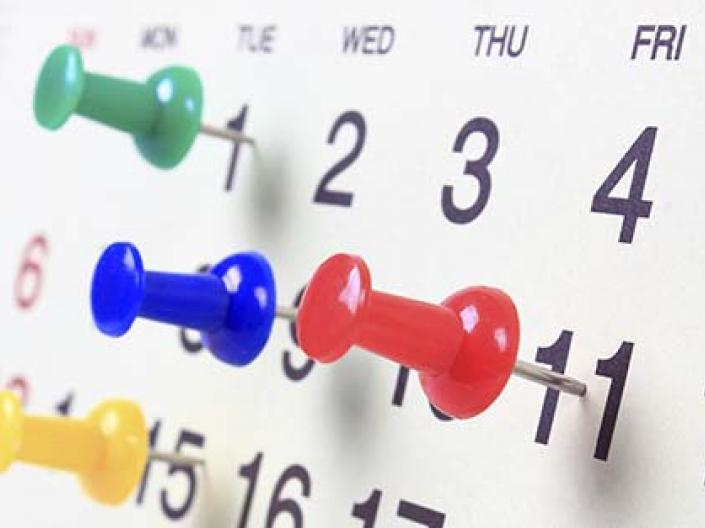 Calendar showing the days of a month with colorful pushpins marking 4 days