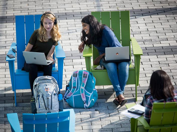 Two female CWRU students sitting in chairs looking at their computers