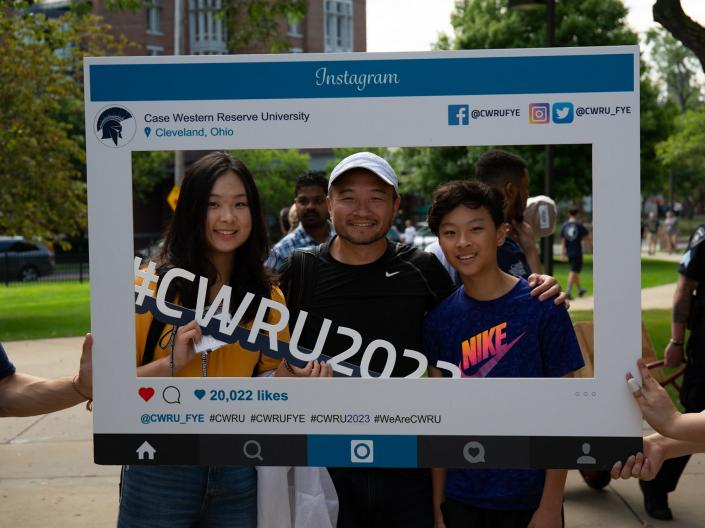 student and their family posing for a photo using an orientation Instagram frame