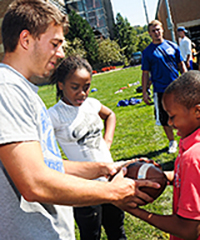 CWRU student playing football with two young people on campus, with students in the background