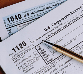 1120 US corporation income and 1040 US individual income tax forms overlaid on each other, with gold pen on top