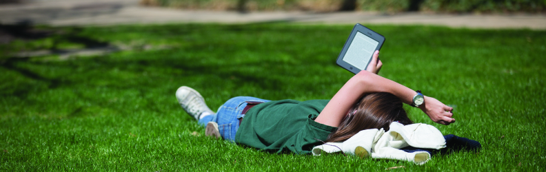 Student reading eBook lying on grass in Quad, summer time