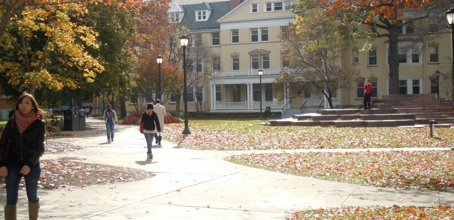 Students walking on Mather Quad in Autumn past Guilford Hall