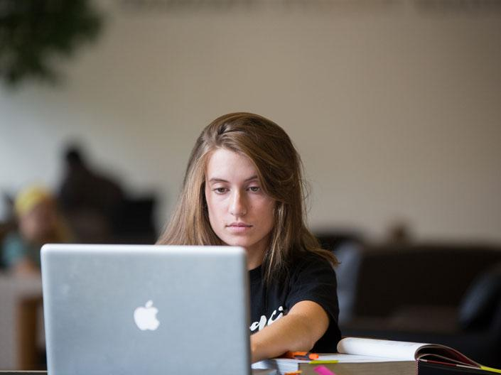 Photo of a female Case Western Reserve University student working on a computer