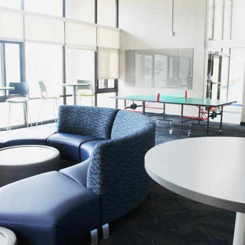 Clarke Tower Lounge with couches, coffee tables, and ping pong table
