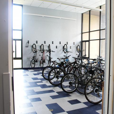Clarke Tower 1st Floor Bike Storage with wall-mounted hooks, bike racks, and several bikes
