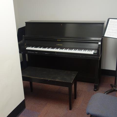 Sherman House Practice Room with common piano, music stands, and sheet music