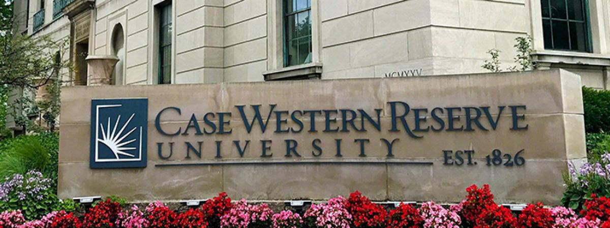 Case Western Reserve University sign with flowers in front.