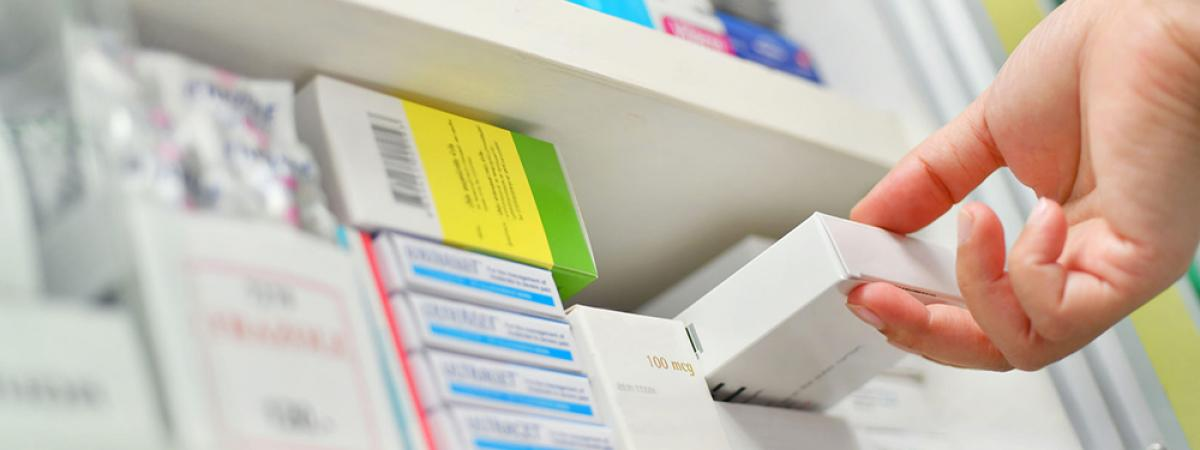 Person removing a prescription from a pharmacy shelf.