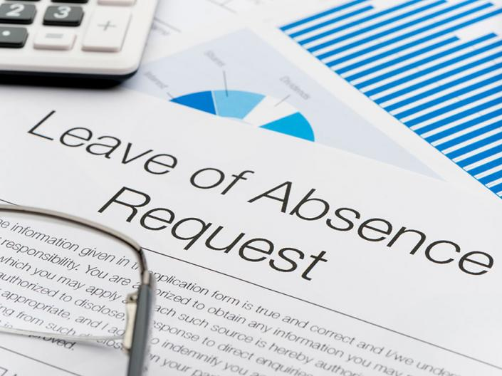 A form with the words Leave of Absence Request with a pair of glasses and a calculator
