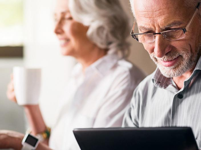 Two older adults looking at their computers