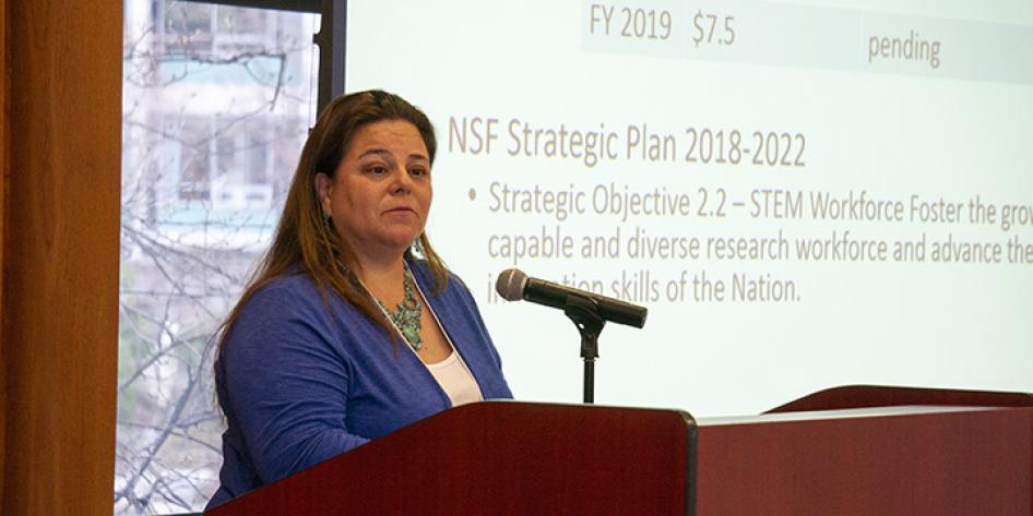 "Woman speaker at Annual Plenary 2018 with a slide that states ""NSF Strategic Plan 2018-2022"""
