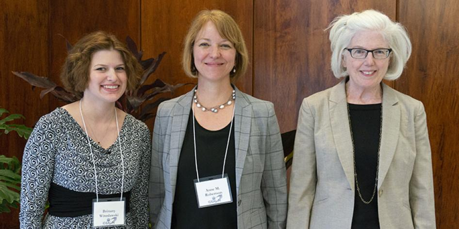 A posed photo of three women smiling at Annual Plenary 2018