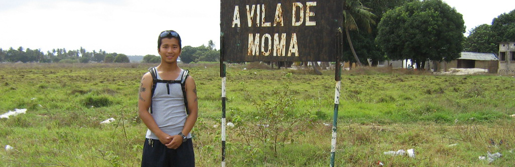 Photo of a student with backpack standing in a rural area near a sign that reads A Vila de Moma