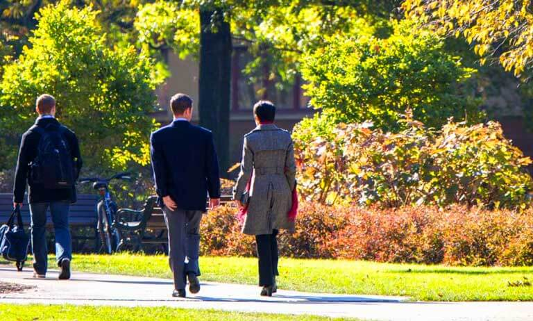 photo of case quad people walking amongst autumn trees