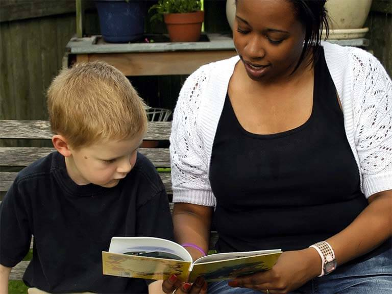 photo of woman reading to child