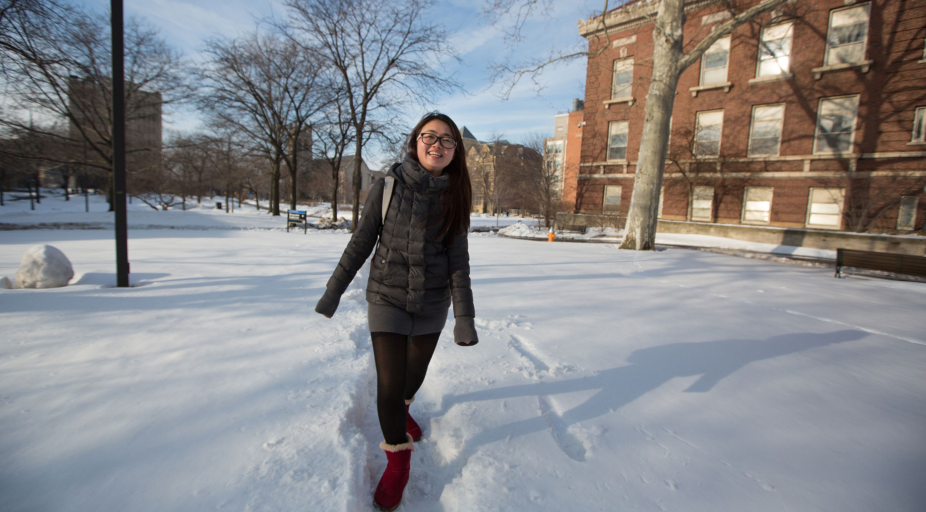 photo of a CWRU female student walking through snow