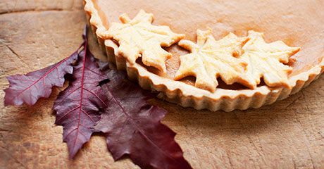 Photo of pumpkin pie, maple leaf cookies and purple leaves on a table