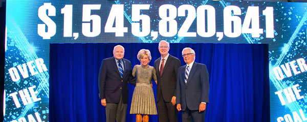 Image of CWRU President Snyder and trustees standing on a stage with the fundraising number of more than $1.5 billion behind them