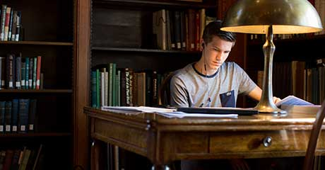 Photo of a student studying at a desk surrounded by bookcases
