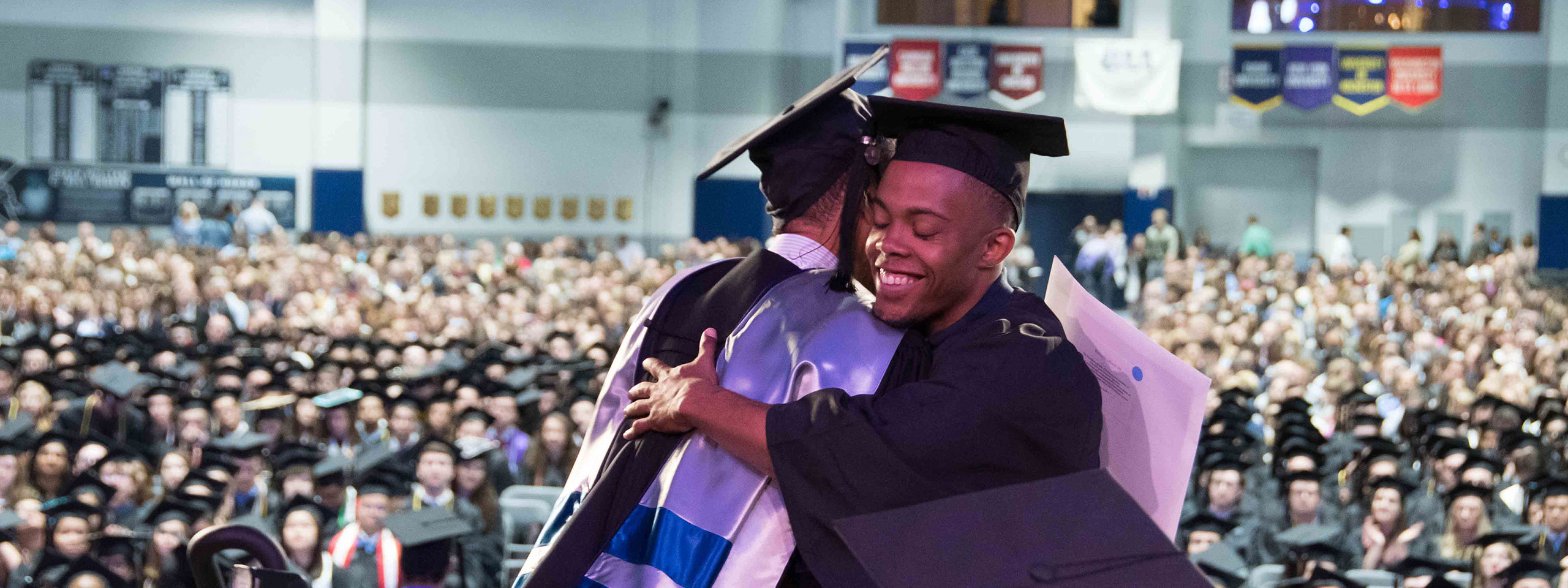 Graduating student hugging at commencement
