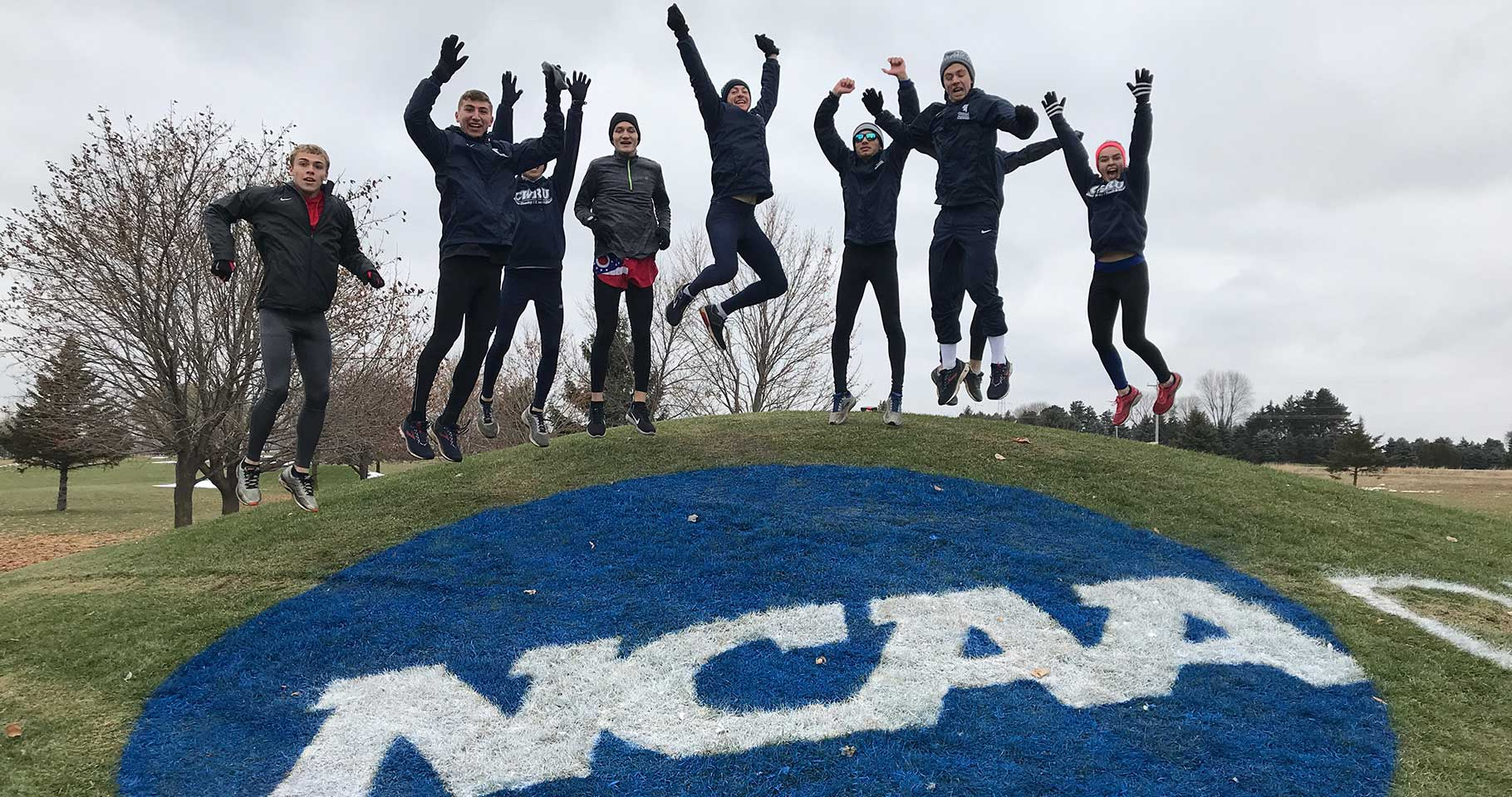 Several members of the cross country teams jump in the air