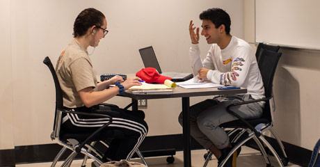 Photo of two students sitting at at a table talking and studying