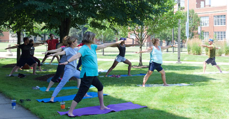 Photo of several people participating in yoga outdoors on campus
