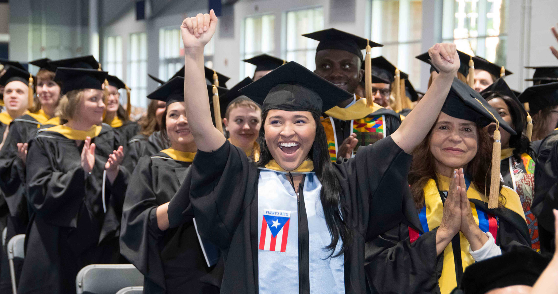 Photo of a CWRU master's degree graduate raising her arms and cheering during commencement ceremony