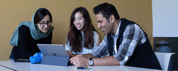 Photo of three international students sitting at a table looking at a tablet