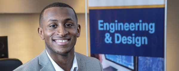 Photo of Terrence Mathis posing for a photo in front of a sign that says engineering and design