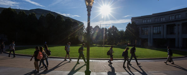 Photo of students walking along the KSL Oval with the sun shining overhead