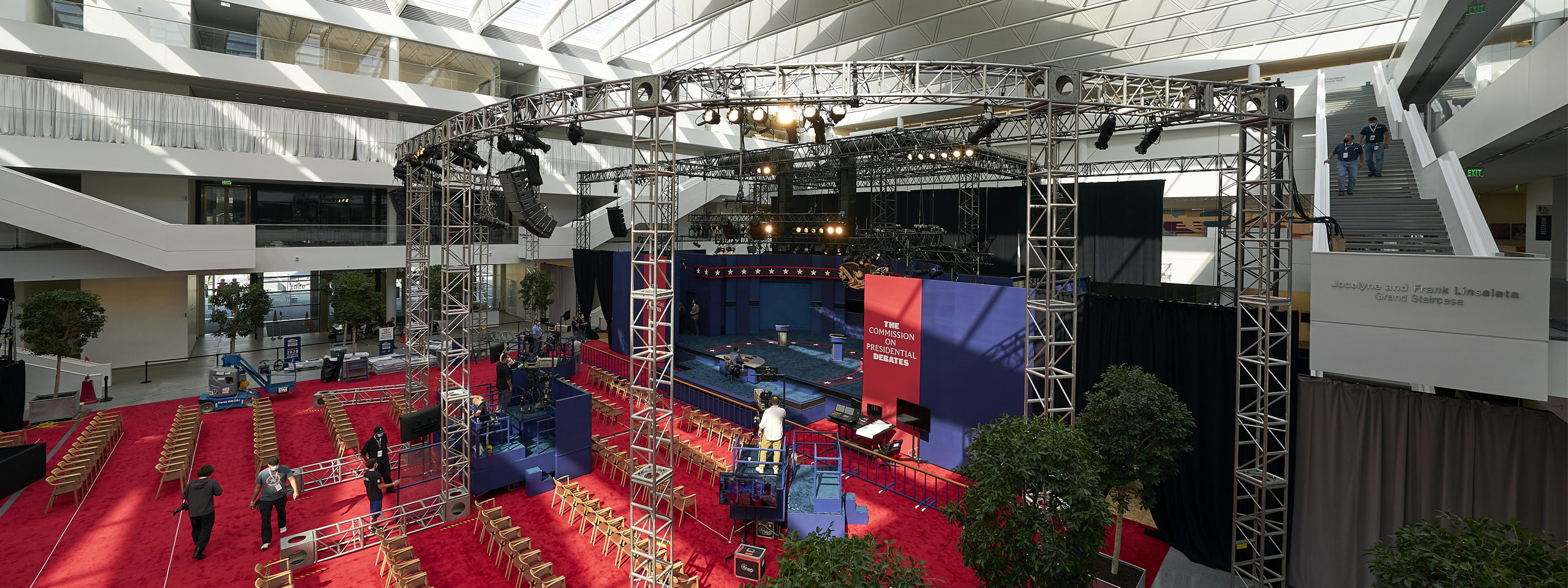 Photo of the interior of the courtyard of the Samson Pavilion with red carpeting lining the floor, the stage set for the debate and trees in planters lining the area