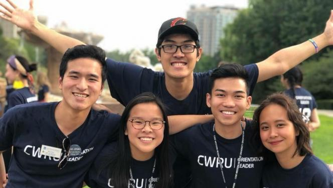 A picture of Lucy and a group of other students standing outside in a group smiling at the camera wearing CWRU Orientation Leader tee shirts