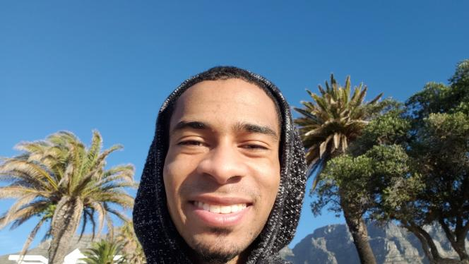 Carlos Lewis-Miller standing outside with his hood on in front of palm trees