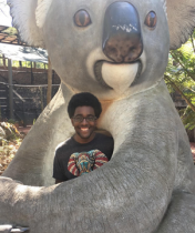 A photo of Miles Booker standing with a statue of a koala bear