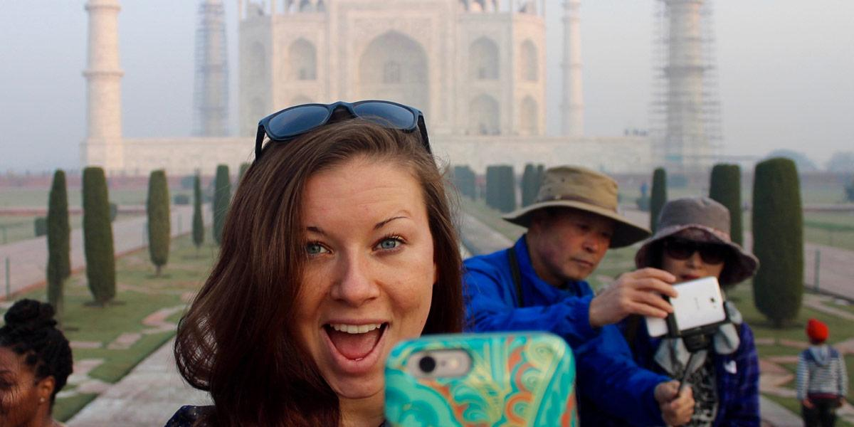 Students taking a selfie in front of the Taj Mahal